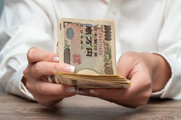 Close up female hand counting Japanese yen back notes, Concept of banking, saving, currency,financial