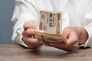 Close up female hand counting Japanese yen bank notes, Concept of banking, saving, currency,financial