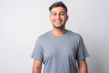 Portrait of happy young handsome Persian man smiling