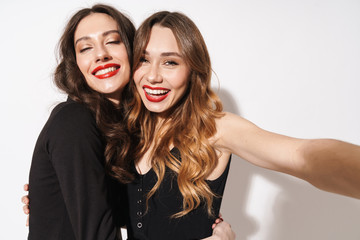Portrait of two smiling women taking selfie photo and hugging Wall mural
