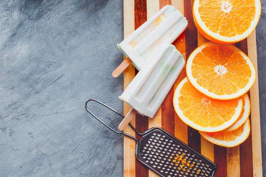 Homemade ice cream coconut and orange Orange ice cream lies next to the fruit on a light background