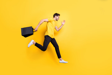Full size photo of handsome guy jumping high holding packages speed rushing sale shopping wear casual t-shirt pants isolated yellow color background Wall mural
