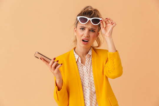 Photo of confused young woman in sunglasses holding cellphone and looking at camera isolated over beige background