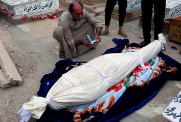 """An Iraqi man reads the Quran next to the body of a demonstrator who was killed at anti-government protests, during a funeral at the """"Valley of Peace"""" cemetery in Najaf"""