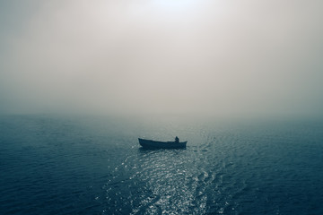 Fishing boat and fisherman in the sea, foggy morning over the water