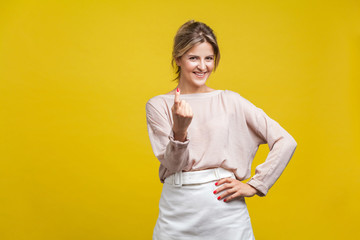 Come here! Portrait of playful happy young woman with fair hair in casual beige blouse standing, calling with finger gesture, inviting to come in. indoor studio shot isolated on yellow background