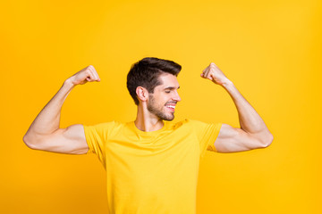 Close-up portrait of his he nice attractive content strong sportive cheerful cheery guy demonstrating muscles isolated over bright vivid shine vibrant yellow color background