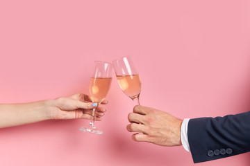 Cropped hands holding glass of champagne isolated over pink background. Unrecognizable couple of man in tuxedo drink glass of champagne with female