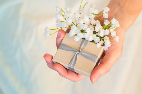 Female hand holds a small gift box and white flowers