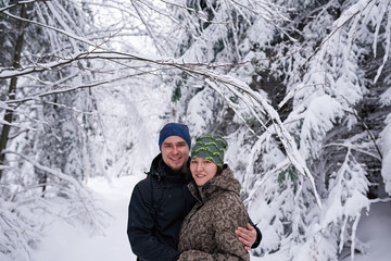 Fototapete - Smiling couple out hiking together in a snow covered forest