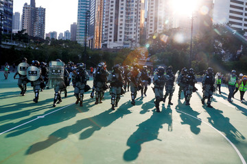 Police in riot gear enter Victoria Park as they disperse an anti-government protesters in Hong Kong