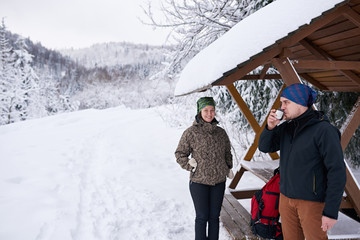 Fototapete - Smiling young couple drinking coffee during a winter hike