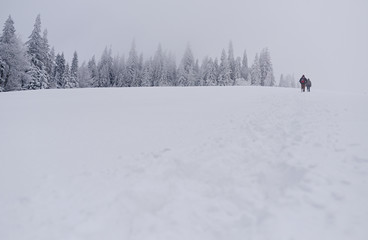 Fototapete - Couple hiking through a snow covered field in the wintertime