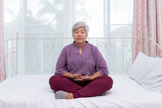 Senior woman female buddhist sitting in lotus position practice meditation, close eyes