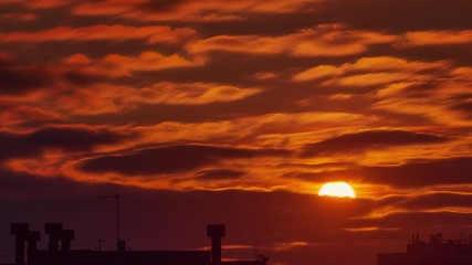 Fotobehang - Beautiful orange sunset clouds moving in sky over city skyline silhouette. Timelapse, 4K UHD.