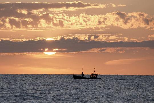 kleiner überladener, romantischer fischerkahn in küstennähe vor der aufgehenden sonne