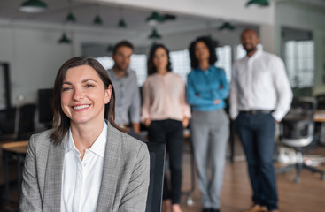 Businesswoman smiling with colleagues standing in the background