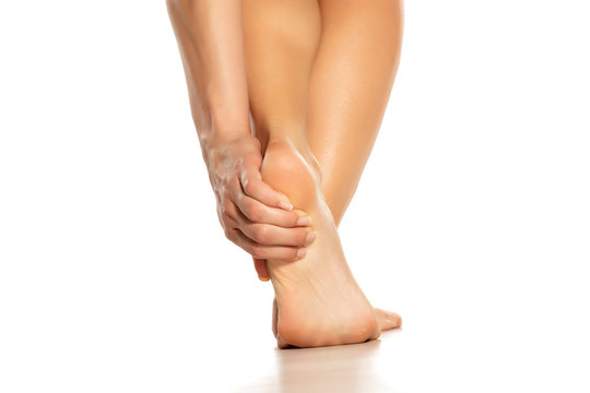 woman holding her painful heel on white background