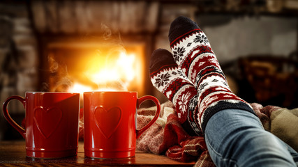 Wall Murals Tea Woman legs with christmas socks and fireplace in home interior.