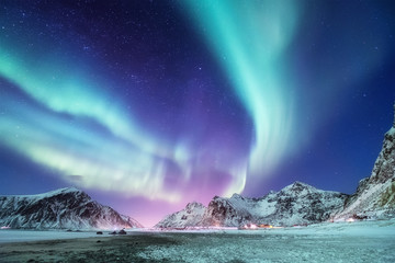 Aurora borealis on the Lofoten islands, Norway. Green northern lights above mountains. Night winter landscape with aurora. Natural background in the Norway