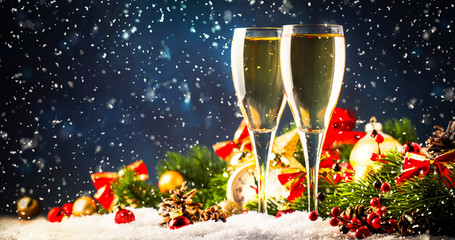 Two champagne glasses and christmas decoration over blue snow golden bokeh background. Happy New...