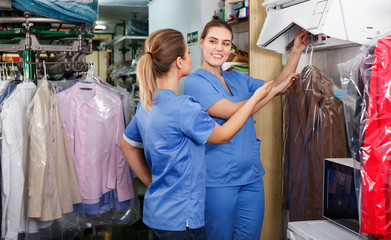 Two young women working in modern dry cleaner