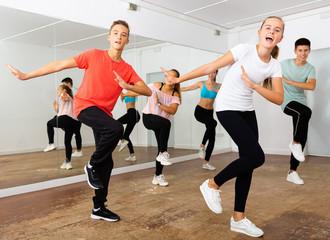 Teenage dancers practicing active vigorous dance in modern studio