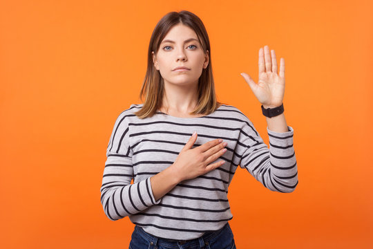 Portrait of faithful beautiful young woman with brown hair in long sleeve striped shirt standing, making promise with hand on chest and palm up, oath. indoor studio shot isolated on orange background