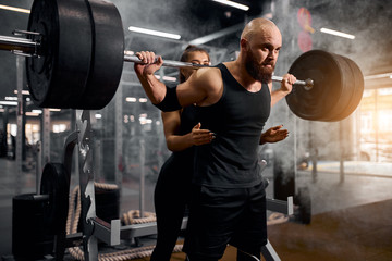 Close view of strong young male powerlifter spending time in gym together with pretty cute female trainer, supporting to lift heavy barbell, training in gym, active people concept