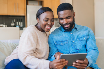 Smiling African American couple using a tablet on their sofa
