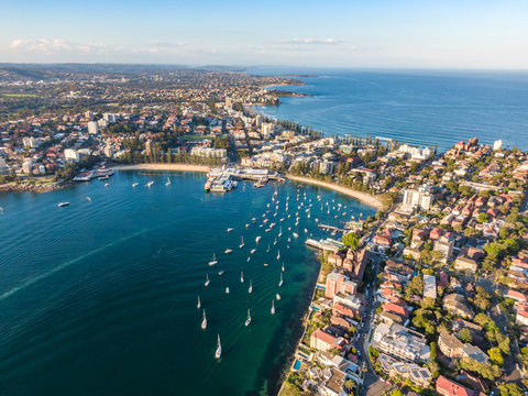 Aerial drone evening view of the Sydney suburb of Manly, a beach-side suburb of northern Sydney, in the state of New South Wales, Australia. Manly Harbour in the foreground, Manly Beach in the back.
