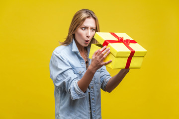 Holiday surprise. Portrait of astonished curious woman in denim shirt looking inside gift box, checking what's inside, unboxing with wow amazed expression. studio shot isolated on yellow background