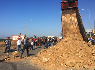 Demonstrators unload sand and stones from a truck to block a road during ongoing anti-government protests in Tripoli
