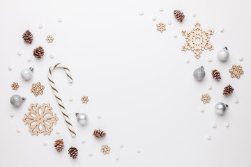 Christmas border made of wooden snowflakes, christmas ornaments, pine cones and white pompons. White background. Flat lay, top view.