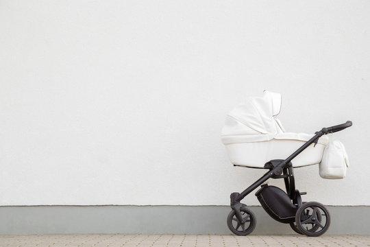 New, white baby stroller on pavement. Empty place for text, quote or sayings on light gray wall background.