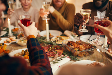 Close up of modern adult people raising glasses while enjoying Christmas dinner at home, copy space