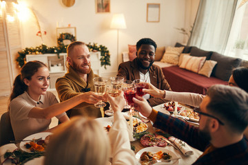 Multi-ethnic group of young people clinking champagne glasses while enjoying Christmas dinner at...
