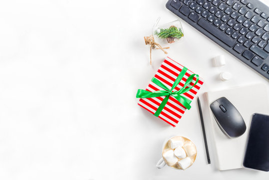 Office secret santa concept with Office table surface, keyboard, mouse, gift boxes and Christmas decoration white background copy space