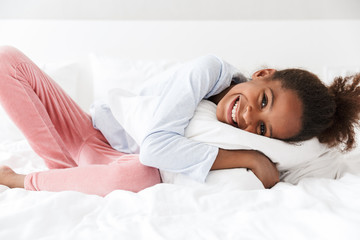 Image of african american little girl smiling and lying in bed at home