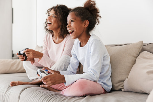 Image of american woman and little girl playing video games with joysticks