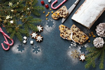 Christmas festive background with german traditional Stollen, cookies,  fir branch, cones and  spices. Overhead view. Copy space