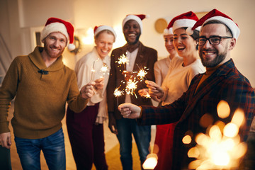 Multi-ethnic group of people holding sparkling lights and looking at camera while enjoying Christmas celebration with friends and family