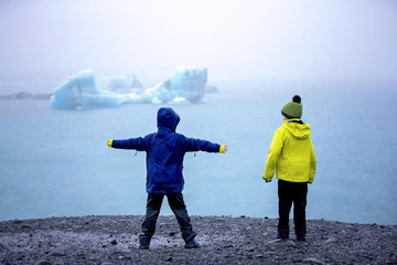 Child, taking picture at early evening on a rainy day at picturesque iceberg lagoon Jokursarlon