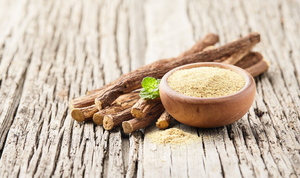 Licorice root with powder and mint leaves on wooden board