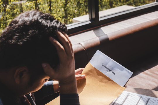 Stressed businessman feeling down after received Termination of Employment Form in paper brown envelope.