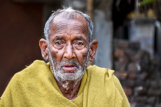 A poor indigenous old man of India looks at the camera with astonished eyes