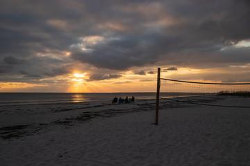 Tourists watch the sunset near recreational volleyball net on Ft. Myers Beach