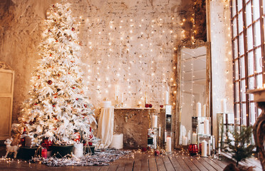 warm cozy evening luxury Christmas room interior design, Xmas tree decorated by gold lights presents gifts, candles,mirror garland lighting fireplace.holiday living room. New year holidays concept