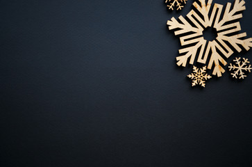 Christmas and New Year background.Hand made rustic wooden snow flakes on black backdrop for winter holidays wallpaper.Empty space for text on poster.Handmade crafts for holiday decor
