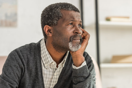 depressed, senior african american man holding hand near face and looking away